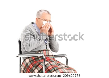 Senior man in wheelchair blowing his nose in a tissue isolated on white background - stock photo