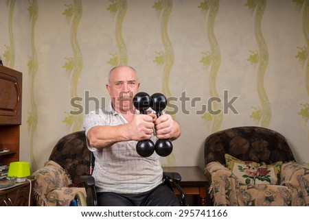 Senior Man in Wheelchair Doing Strength Exercises as part of Rehabilitation with Handheld Dumbbells at Home in Living Room