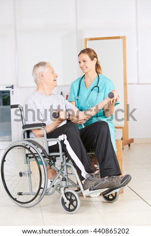 Senior man in wheelchair lifting dumbbells in physiotherapy