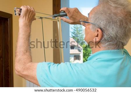 Senior man installing measuring shower box stock photo 490056550 senior man installing a shower box at home do it yourself concept solutioingenieria Gallery