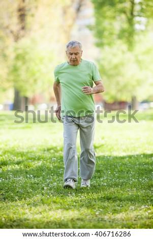 Senior man is jogging in park. Active retirement. - stock photo