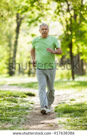 Senior man is jogging in park. Active retirement. - stock photo
