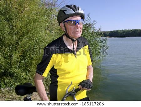 Senior man is riding his old bike on the Danube dam. - stock photo