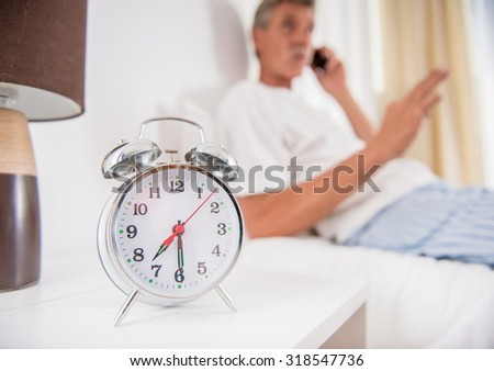 Senior man is sitting in bed and talking by phone. Focus on alarm clock.