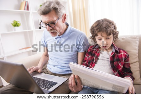 Senior man is working with a laptop wile sitting with a cute boy with newspaper. - stock photo
