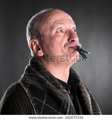 Senior man keeping silence with closed mouth by clothespin  on a dark background