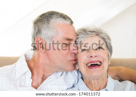 Senior man kissing happy wife sitting on sofa at home