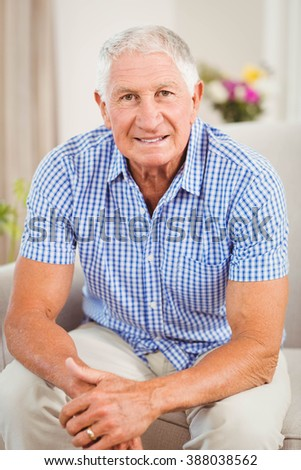 Senior man looking at camera and smiling in living room - stock photo