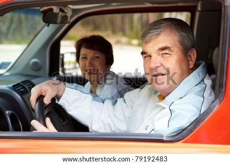 Senior man looking at camera in the car with his wife on background - stock photo