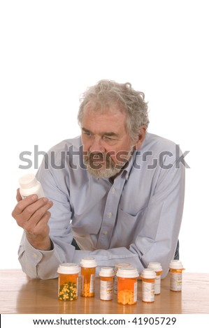 Senior man looking at his medication bottles set against a white background.