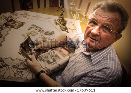 Senior man looking at old photographs. Reminisce about the past - stock photo
