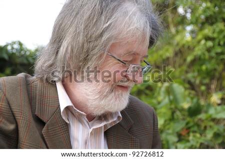 Senior man looking at something that makes him smile. - stock photo