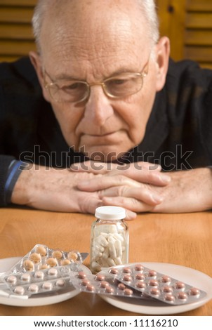 Senior man looking resigned to the pills he has to take (focus on pills) - stock photo