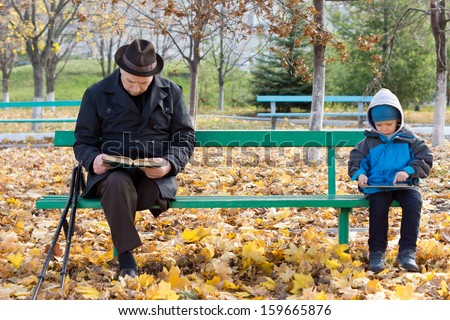 Senior man on crutches reading a book with his little grandson sitting on the opposite end of the wooden park bench playing on a tablet computer