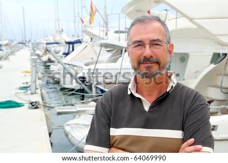 Senior man on marina sport boats portrait happy relaxed - stock photo