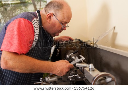 senior man operating lathe machine in workshop - stock photo