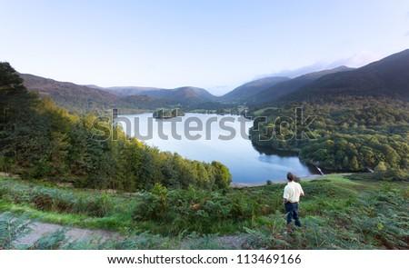 Senior man overlooks Grasmere in Lake District as sunrise as sun light mountains - stock photo