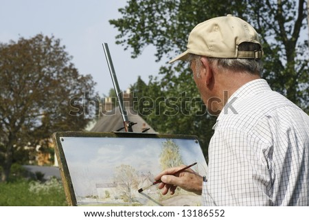 Senior man painting in a hat. - stock photo