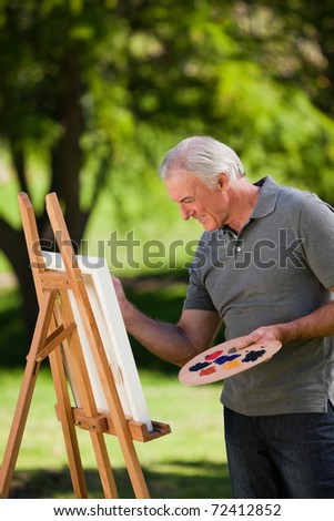 Senior man painting in the garden - stock photo