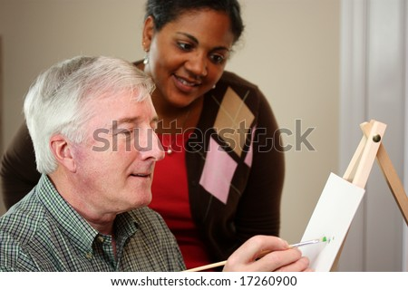 Senior Man Painting With Brush And Canvas - stock photo