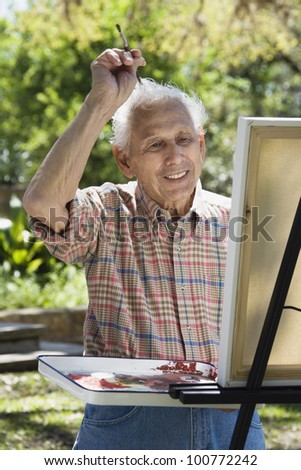 Senior man painting with easel outdoors