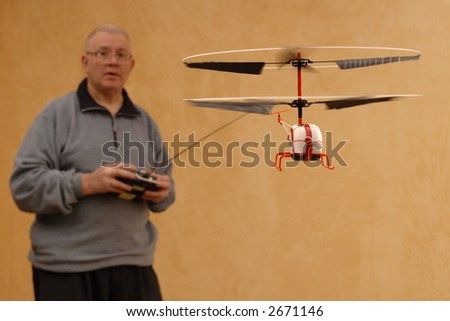 Senior man piloting a tiny radio controlled helicopter indoors.  Shallow DOF with focus on helicopter. - stock photo