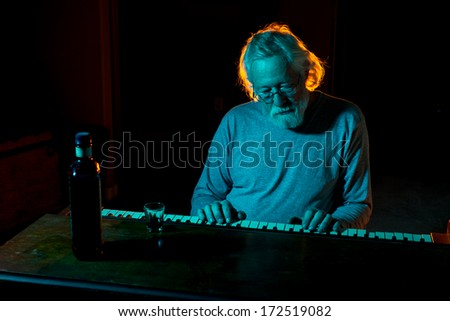 Senior man playing an old piano while drinking alcohol with dramatic lighting in blues and oranges - stock photo