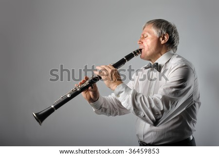 senior man playing clarinet - stock photo