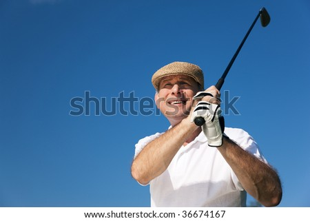 Senior man playing golf looking after the ball in front of a clear blue sky - stock photo