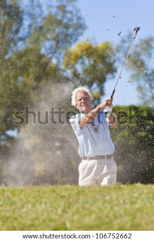 Senior man playing golf shot in a sand bunker - stock photo
