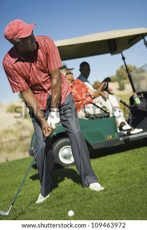 Senior man playing golf with people sitting golf cart in background
