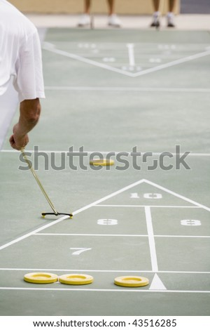Senior man playing shuffleboard - stock photo