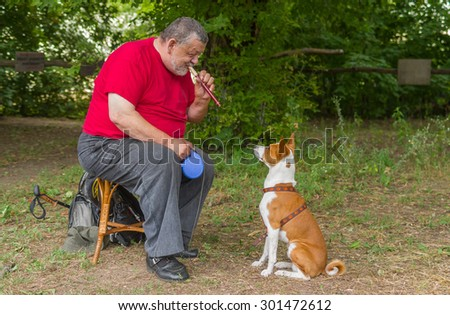 Senior man plays his basenji dog a melody with fife - stock photo