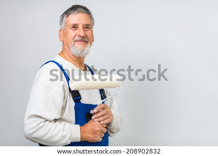 Senior man posing with a paint roller after having paint a white wall - stock photo
