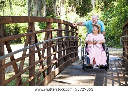 Senior man pushes his disabled wife's wheelchair through the park. - stock photo