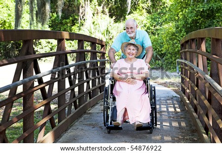 Senior man pushes his disabled wife through the park in a wheelchair. - stock photo