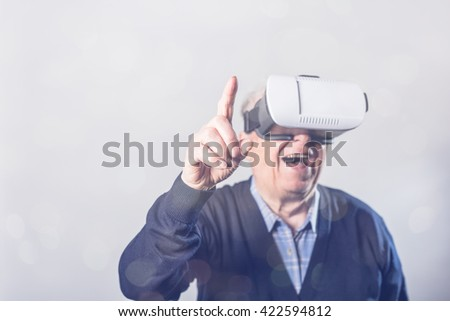 Senior man reaching to touch something with his finger while wearing VR headset - stock photo
