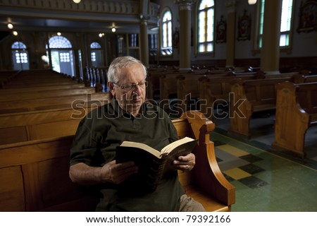 Senior man reading a bible in church - stock photo