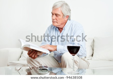 Senior man reading a book on the couch in the living room