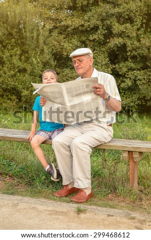 Senior man reading and bored cute child looking over the newspaper sitting on park bench. Two different generations concept.