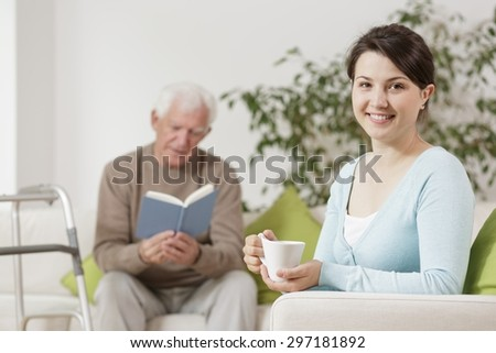 Senior man reading book and granddaughter drinking tea - stock photo