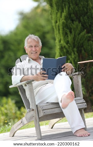 Senior man reading book in pool deck chair - stock photo