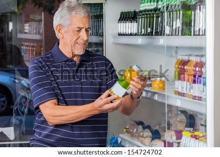 Senior man reading information on juice bottle at supermarket - stock photo