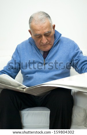 Senior man reading newspaper - stock photo