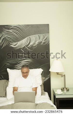 Senior Man Reclining in Bed Using Laptop