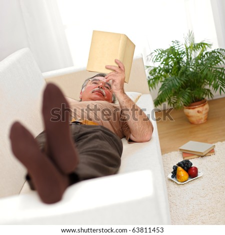 Senior man relaxing and reading books on sofa