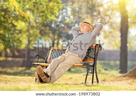 Senior man relaxing in park on a sunny day seated on a wooden bench - stock photo
