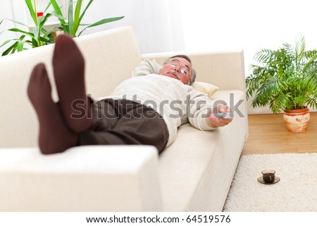 Senior man relaxing on sofa and looking to television
