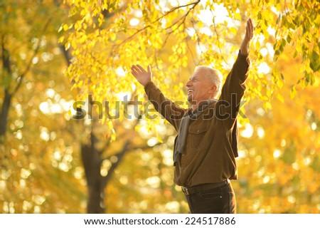 Senior man resting in the park in autumn - stock photo