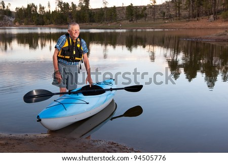 Senior Man Resting on Kayak Overlooking Rural Lake
